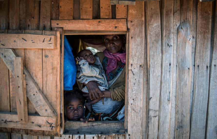 Sija Marcelline, with her two children, looks through the window of her house in Amboasary