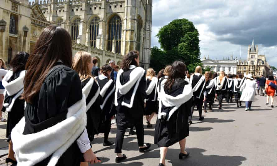 Students in graduation gowns walking past Kings College in Cambridge