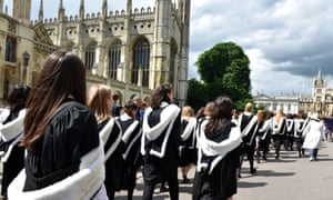 Cambridge students pass by King's College on their way to graduation.