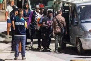 Migrants board vans after leaving the Ocean Viking.