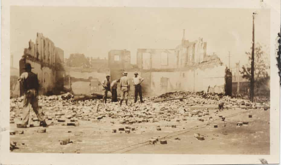Black Tulsa residents stand in front of a leveled building in Greenwood after the violence subsided.