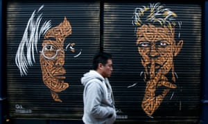 A painting of David Bowie and John Lennon on shop shutters in Brixton market
