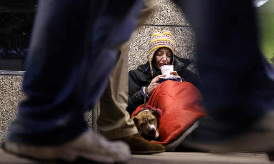 A homeless woman sits huddled under a sleeping bag next to her dog in London