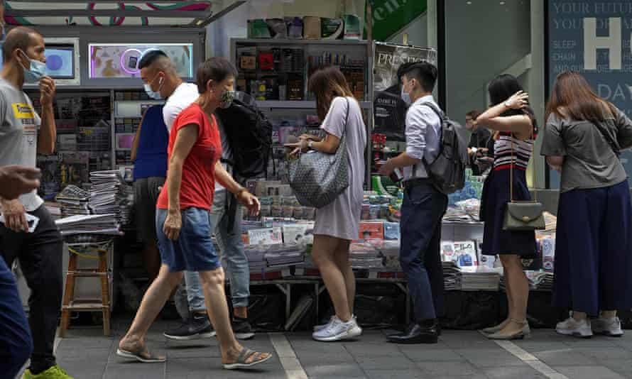 People queue up to buy the Apple Daily newspaper in downtown Hong Kong