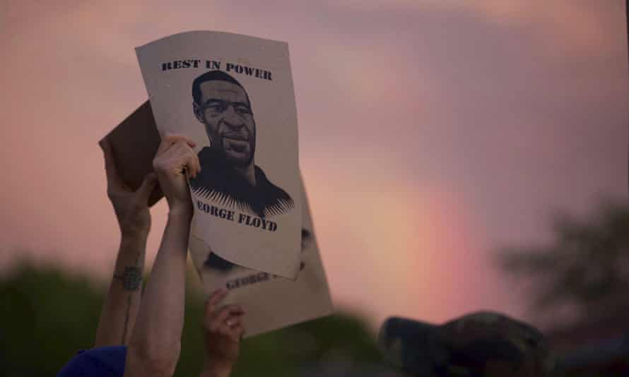 A demonstrator holds a sign with an image of George Floyd during protests in Minneapolis, Minnesota, on 27 May.
