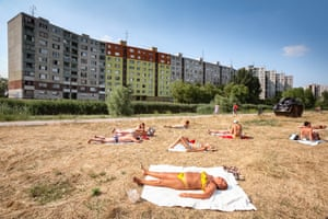 """Bratislava, Slovakia. Longitude: 17¡ 11' 34.16"""" Residents sunbathe outside their homes in Petržalka. The city's largest borough is made up almost entirely of concrete tower blocks that were built across the eastern bloc during the communist era"""