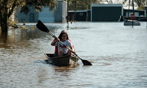 Residents paddle through a flooded neighborhood after Hurricane Delta passed over Delcambre, Louisiana