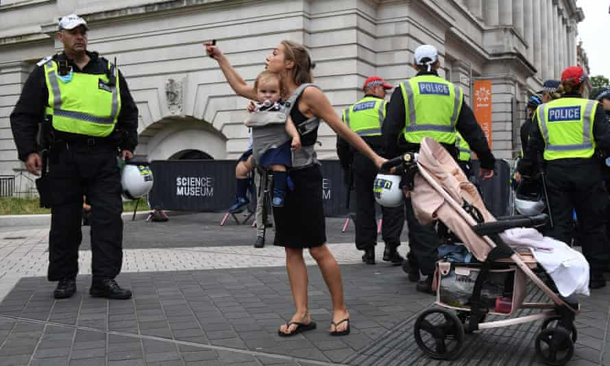 A woman with a baby in a sling and holding one handle of a pushchair gestures towards the face of a police officer
