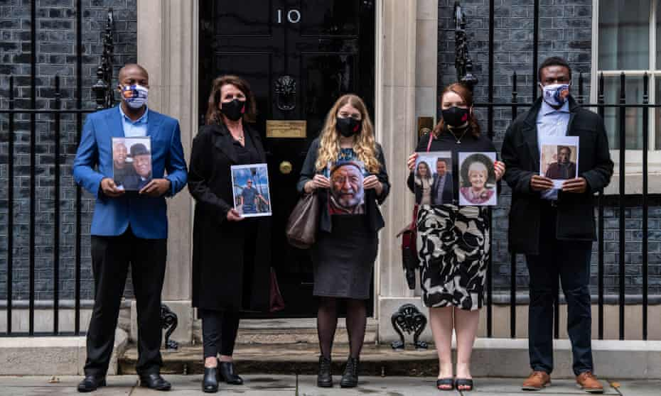 The Bereaved Families for Justice delegation outside 10 Downing Street holding photos of their deceased relatives after meeting Boris Johnson.