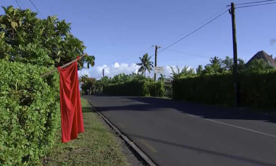 Red flags hang outside homes in Samoa where families are requesting vaccination against measles.