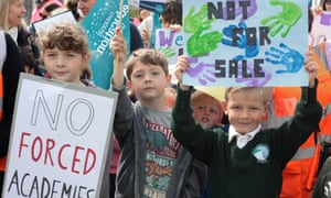 Children hold up signs protesting against converting schools to academies