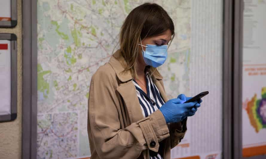 A woman wearing a mask and gloves uses a mobile phone while waiting for an underground train in Milan, Italy