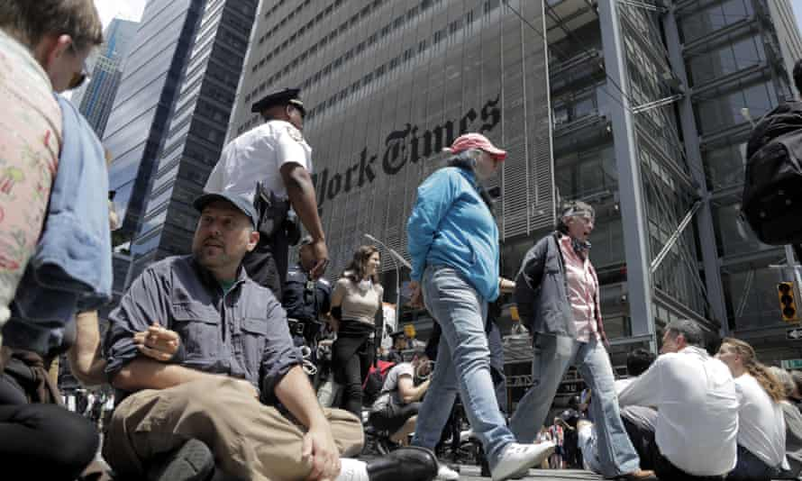 Activists block traffic outside the New York Times office during a sit-in to demand coverage of climate change by the newspaper.