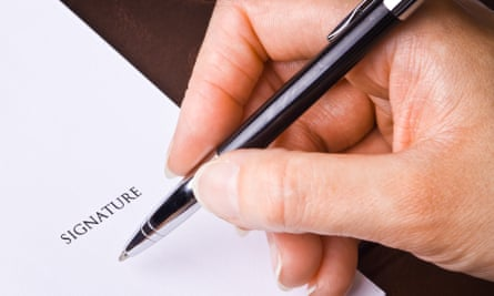 A hand with a pen signing a document