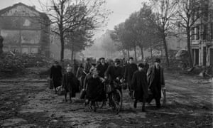 Families leave their town following the bombing campaign in Aachen, Germany