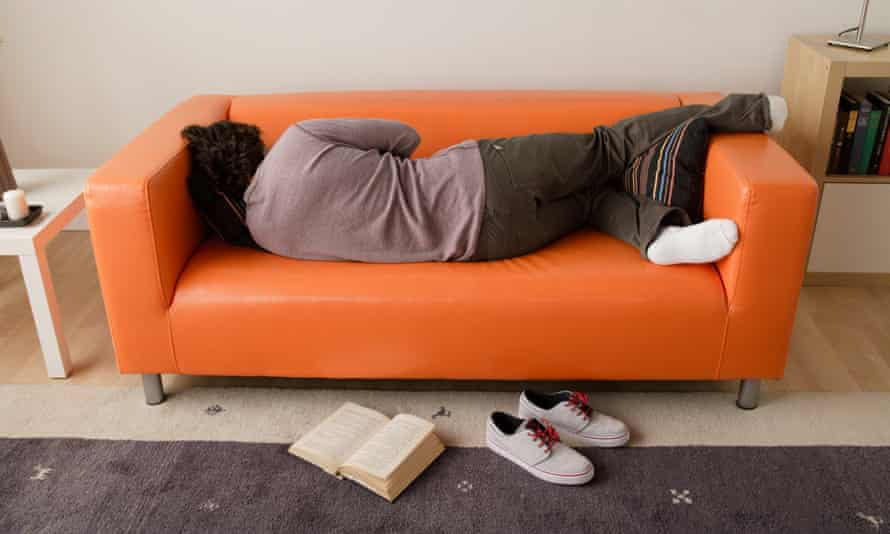Man lies sleeping on sofa with back to book on floor
