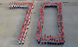 """Students form a massive """"70"""" as they pose with Chinese national flags and red stars for the 70th anniversary of China's Victory Day."""