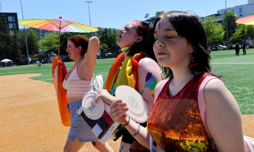 Frances Wilson, Claire Kilga and Raven Seydlitz participate in the Capitol Hill Pride march in soaring heat in Seattle on Saturday.