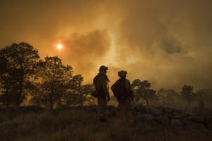 Firefighter Jake Hainey (left) and engineer Anna Mathiasen watch as a wildfire burns near Oroville