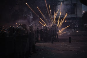 Fireworks thrown by anti-government protesters explode over riot police during clashes