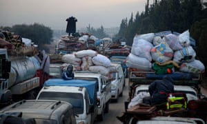 Families from the south of Idlib province drive towards the Syrian-Turkish border
