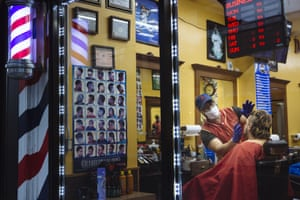 A barber wears a protective mask and gloves while cutting a customer's hair at a shop in New Rochelle, New York.
