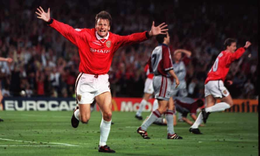 Teddy Sheringham celebrates with his arms outstretched running towards the camera after scoring the equalising goal for Manchester United against Bayern Munich in the 1999 Champions League final.