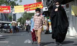 An Iranian woman and her son wearing protective face masks walk the street in Tehran, Iran.