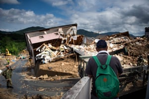 A man looks out at a damaged house in a flood-hit area in Kumano
