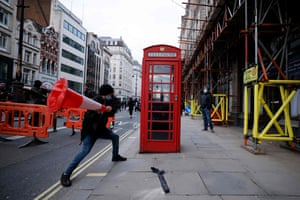 A demonstrator prepares to strike a telephone box with a road cone during a 'Kill The Bill' protest against the Government's police, crime, sentencing and courts bill in London.