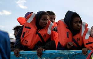 Migrants wait to be rescued as they drift in a boat