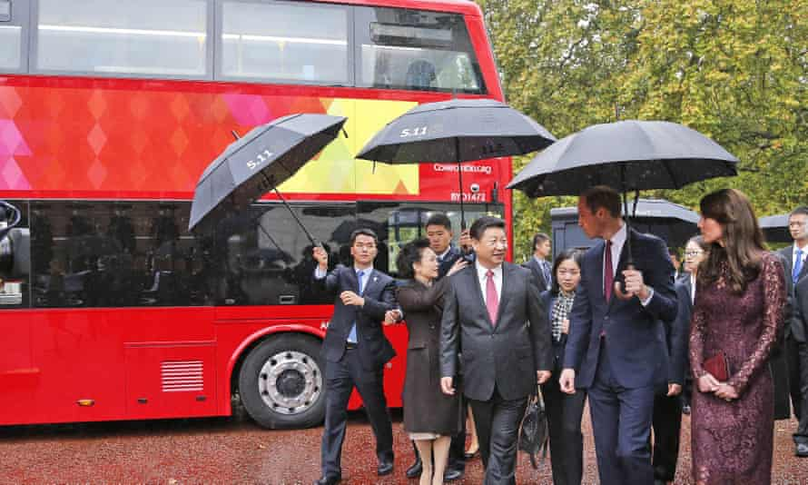 Xi is accompanied by his wife Peng Liyuan (left) and the Duke and Duchess of Cambridge as they walk past a London bus.