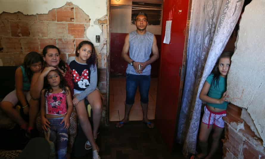 Residents Juliana Antonachi, husband Diego Paula Silva and their four daughters, stand in their apartment at the Mauá building