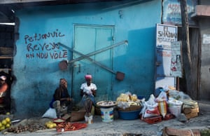 Street traders sit in front of political graffiti in Pétion-Ville on the outskirts of Port-au-Prince