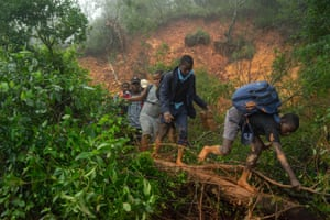 School students walk past a mudslide covering a major road at Skyline junction in Chimanimani, Manicaland Province, Zimbabwe, on 17 March.