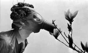 "A Pace College student in a gas mask ""smells"" a magnolia blossom in City Hall Park on Earth Day in 1970 in New York. (AP Photo)"