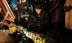 The prime minister, Justin Trudeau, places a candle on Parliament Hill during vigil for the victims who were killed in a plane crash in Iran in Ottawa, Canada.