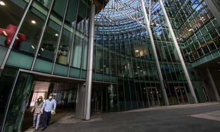 Two people walk through an empty office building complex in the City of London.