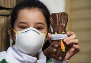 A 12 year-old girl in Lexington, US, holds a chocolate Easter bunny with a homemade face mask