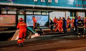 Chinese rescuers prepare to lift a bus out of the ground after the road collapse in Xining.