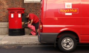 A Royal Mail employee empties a post box