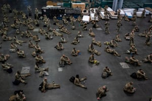 US Army personnel sit apart at the Jacob K Javits Convention Center in New York City, which will be partially converted into a hospital.