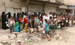Displaced people queue up to receive aid food in Aleppo, Syria.