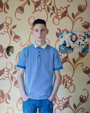 Paddy, 16, standing in front of patterned wallpaper