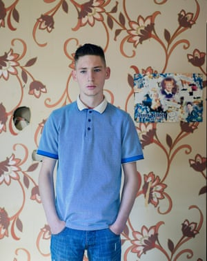 Paddy, a Traveller from Liverpool, standing in front of patterned wallpaper