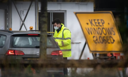 A medical worker speaks with an NHS worker as they attend a drive-through COVID-19 testing centre in a car park in London.