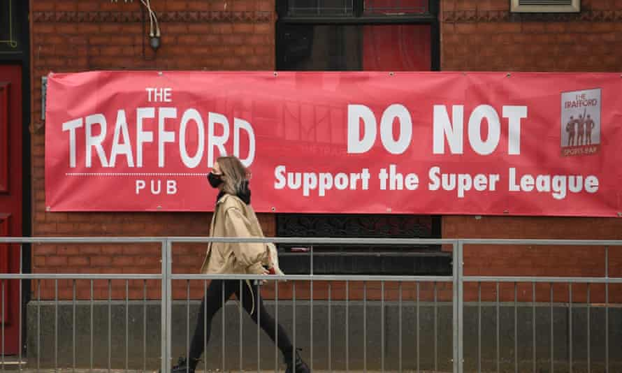 A woman passes a banner saying Trafford Pub do not support the ESL
