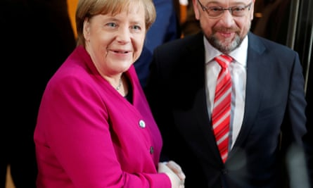 Angela Merkel and Martin Schulz shake hands before exploratory talks about forming a new coalition government.