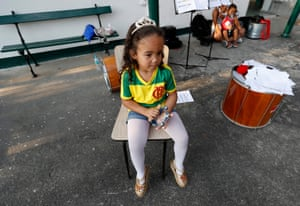 The younger sister of a Favela Brass band member watches on