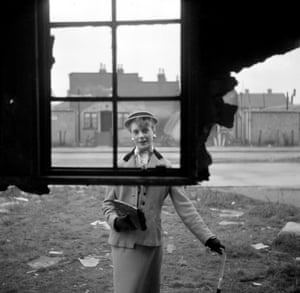 18 year old Barbara Wood of Plaistow models her boater and embroidered blouse through a paneless window